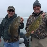 two men show off their smallmouth bass catch on the shores of lake erie